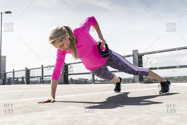 Woman training with dumbbells- doing one-armed plank