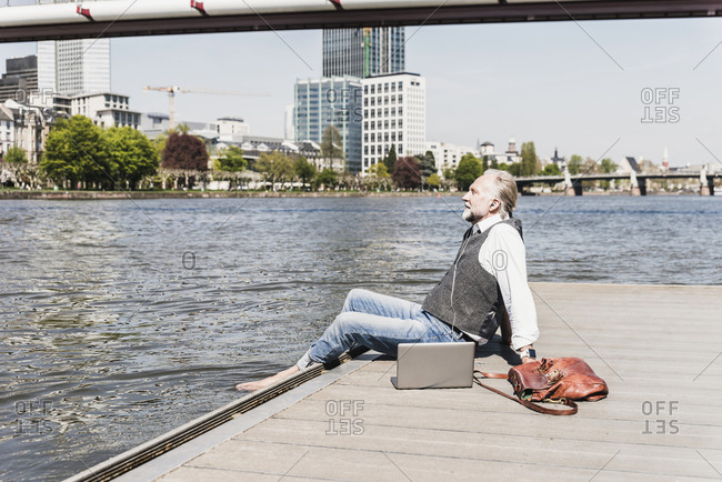 Mature man with laptop and earbuds sitting at the riverside in the city