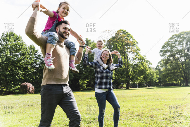 Happy parents carrying children on shoulders in a park