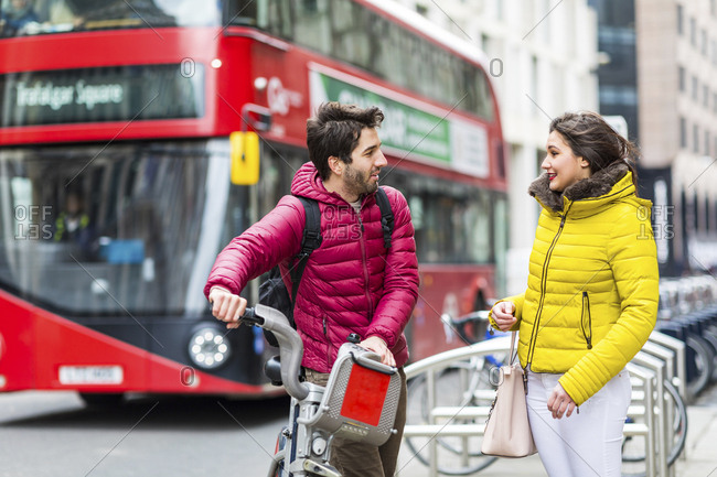 UK- London- young man with rental bicycle from bike share stand  talking to his girlfriend