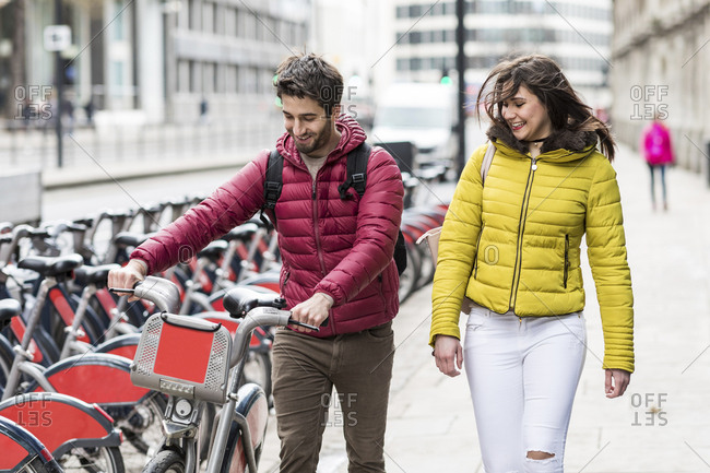UK- London- young couple with rental bicycle from bike share stand