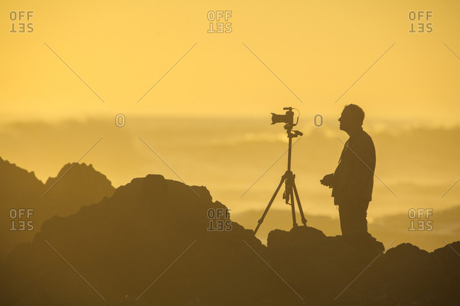 Africa- South Africa- Cape Town- Silhouette of photographer at beach in the evening light