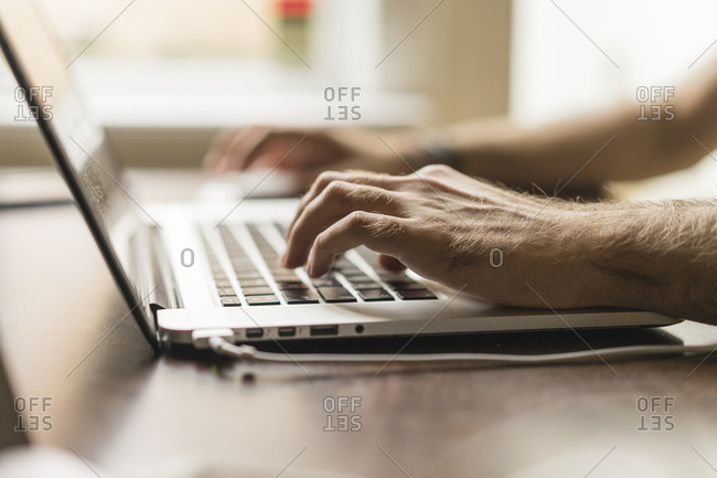 Man's hand on keyboard of laptop- partial view