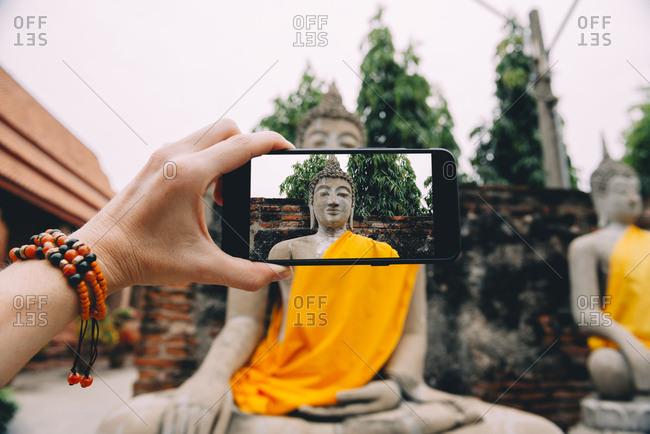 Thailand- Ayutthaya- Wat Yai Chai Mongkhon- taking a photo from Buddha with smartphone