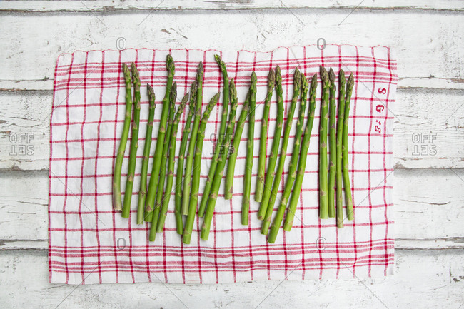 Organic green asparagus on red-white kitchen towel