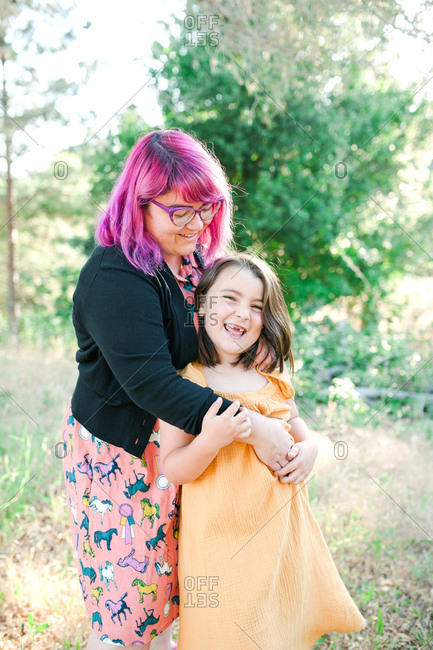 Portrait of a woman with pink hair hugging daughter