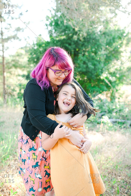 Woman with pink hair hugging daughter