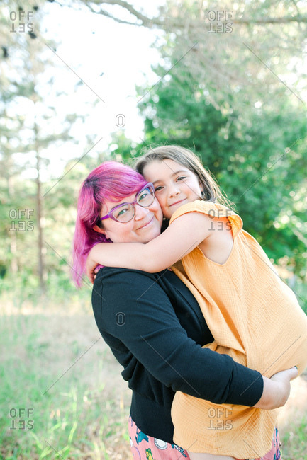 Woman with pink hair holding daughter