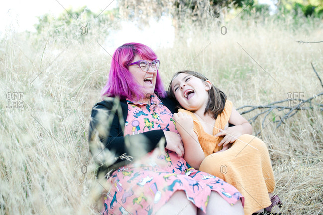 Woman with pink hair sitting with her daughter laughing