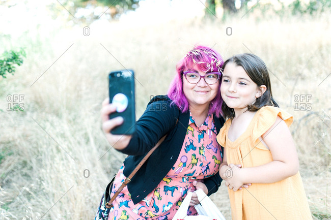 Woman with pink hair sitting taking selfie with her daughter