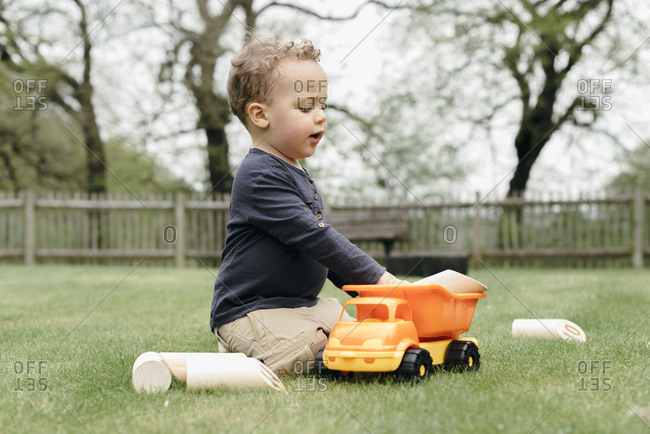 Child plays with toy truck in grass