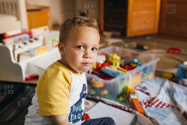 Young boy sits on floor in his playroom
