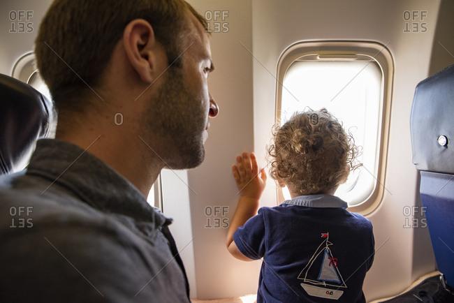 Young boy looks outside in flight