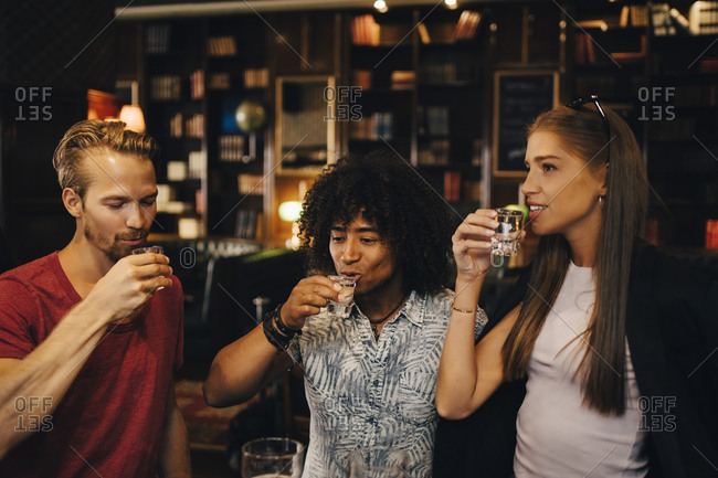 Male and female friends enjoying tequila shots at bar