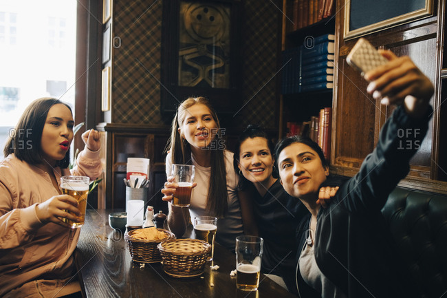 Woman taking selfie while enjoying beer with friends at restaurant