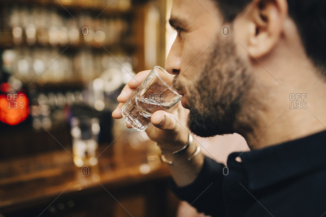 Mid adult man drinking tequila at bar
