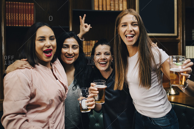 Portrait of happy female fans toasting beer glasses while celebrating at restaurant