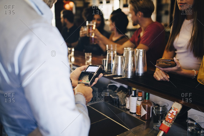 Cropped image of bartender using credit card reader while receiving payment from customers at bar