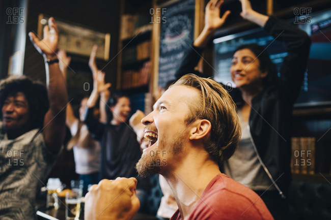 Excited man watching match with friends at pub