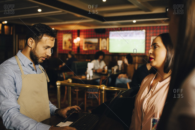 Female customers ordering male waiter using laptop at pub