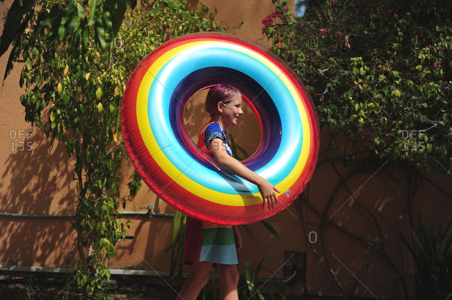 Girl carrying a colorful rainbow swim ring