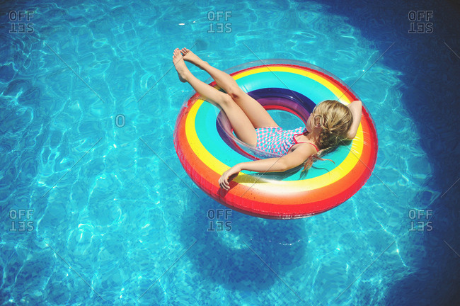 Girl relaxing on a colorful rainbow swim ring in swimming pool