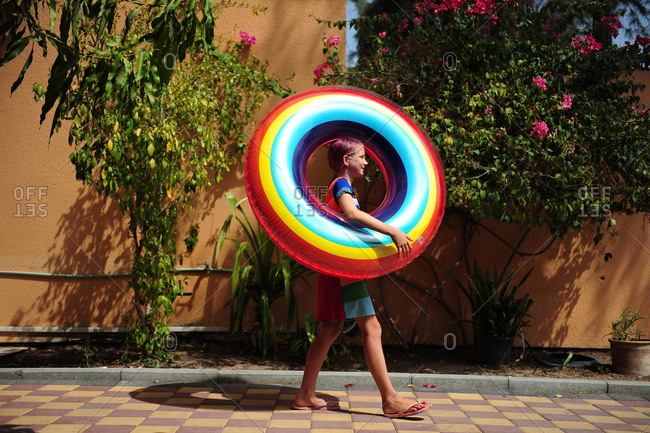 Girl carrying a rainbow swim ring