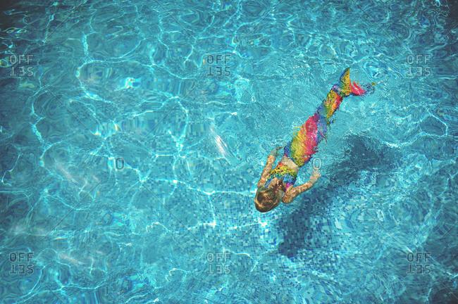 Girl in mermaid costume swimming underwater in pool