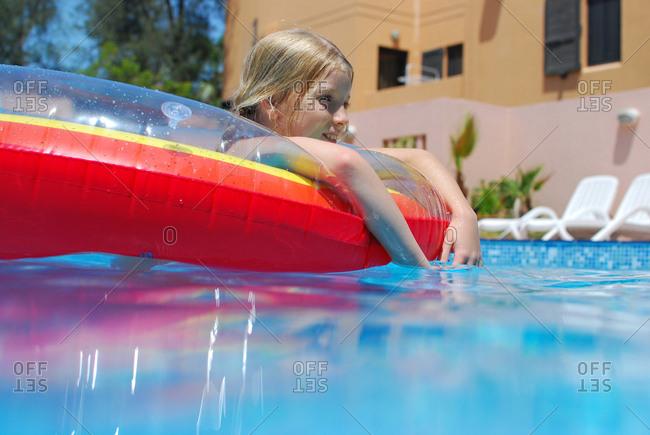 Girl floating on swim ring in swimming pool