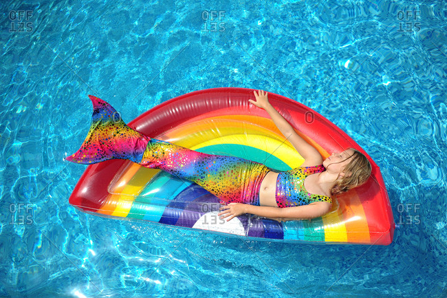 Girl in mermaid costume relaxing on rainbow float in swimming pool