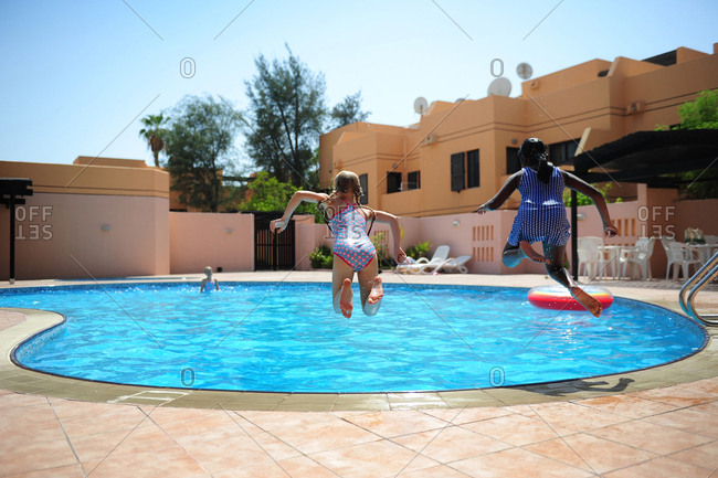 Two girls jumping into swimming pool together