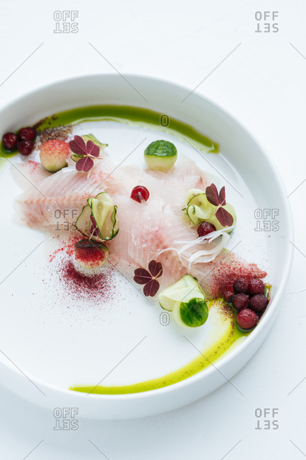 Cropped view of vibrant lingonberry fish served on minimalist dinnerware