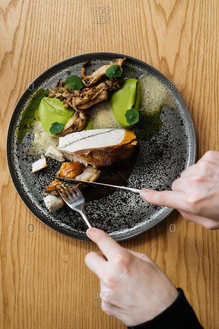 Top view of two hands cutting modern gourmet dinner
