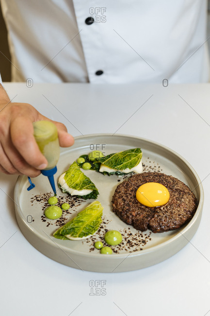 Gastro chef adding sauce to plate