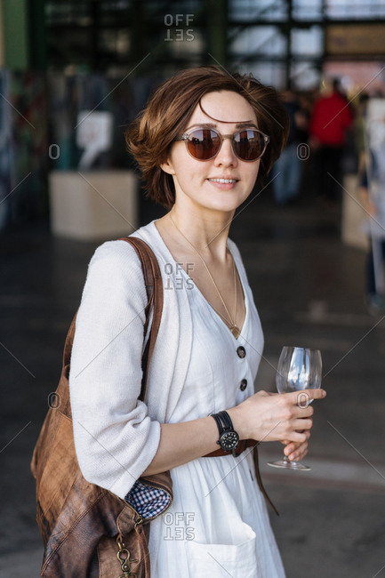 Woman walking with glass stemware outside store