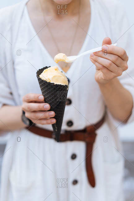 Woman eating spoonful of vanilla ice cream from cone