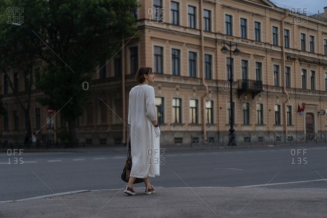 Woman in long loose dress walking home at sunset