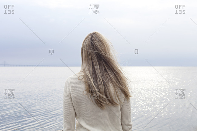 Blonde woman staring at ocean from behind