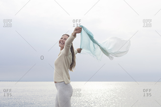 Blissful woman prancing by ocean with long scarf behind her