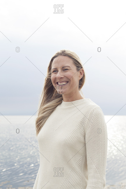 Blonde tourist standing in front of ocean at sunset