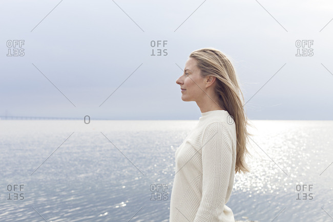 Side view of woman in sweater staring across beach