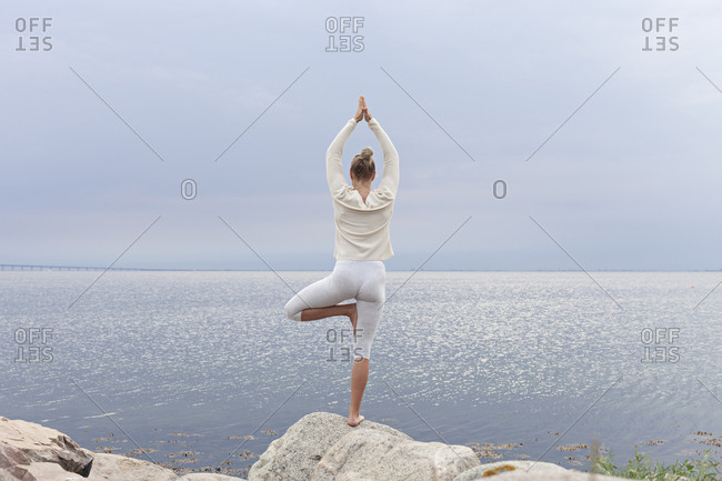 Woman centered on beach rock in yoga pose