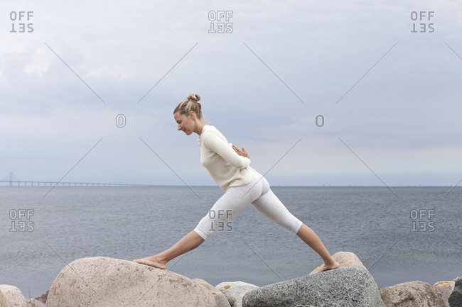 Yoga trainer practicing on natural ocean rocks