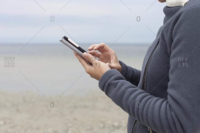 Side view of hands holding up smartphone on the beach