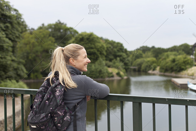 Backpacker stops at bridge to admire river view