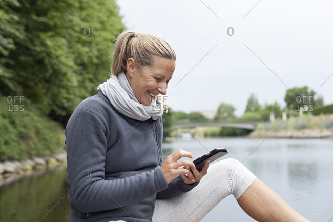 Happy woman texting in activewear at public park