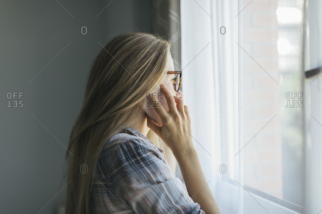Portrait of a young woman talking on her phone while looking out window