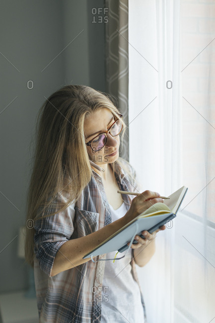 Young woman writing in notebook while talking on phone and standing in front of window
