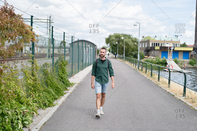 Young man in shorts walking to bus stop