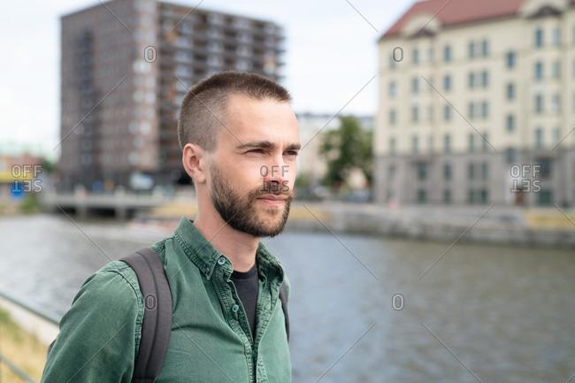 Young man with facial hair staring off camera